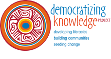 Logo of Democratizing Knowledge Collective. It is a circle with an Indigenous-inspired glyph in orange, teal, gold, and red. The following legend is part of the logo: developing literacies, building communities, seeding change.